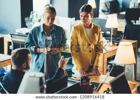 Startup and millenial business concept. Two cheerful women discussing projects with manager