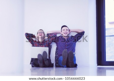 startup business and new mobile technology concept with young couple in modern bright office interior working on laptop and tablet computer on new creative project and brainstorming