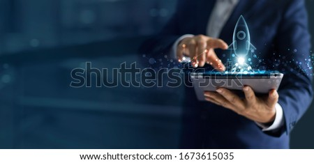 Startup business concept, Businessman holding tablet and icon transparent rocket is launching and soar flying out from screen with network connection on dark blue modern background. Stock photo ©