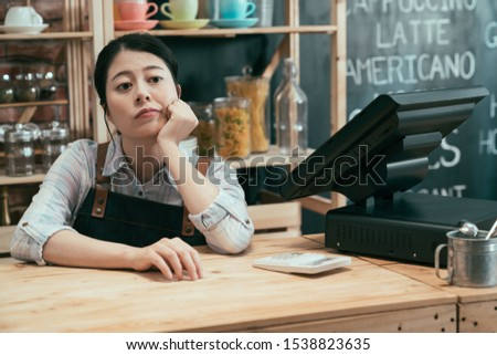 startup business owner woman waiting for customers leaning on bar counter with hands on chin. upset asian japanese lady waitress feels bored and depressed with bad poor finance in cafe restaurant.