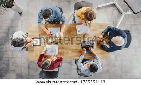 Startup Meeting Room: Team of Entrepreneurs sitting at the Conference Table Have Discussions, Solve Problems, Use Digital Tablet, Laptop, Share Documents with Statistics, Charts. Top View