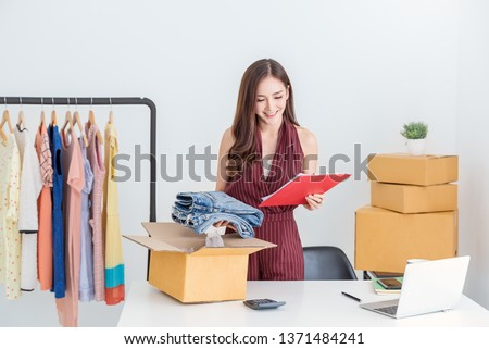 Startup small business entrepreneur SME, asian woman packing cloth in box. Portrait young Asian small business owner home office, online sell marketing delivery, SME e-commerce telemarketing concept