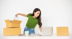 Startup small business entrepreneur SME, asian woman packing product into box. Portrait young Asian small business owner homeoffice, online sell marketing delivery, SME ecommerce telemarketing concept