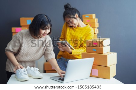 Startup small business owner working with computer at workplace. Freelance two woman seller check product order. Packing goods for delivery to customer. Online selling. E-commerce. Online Shopping