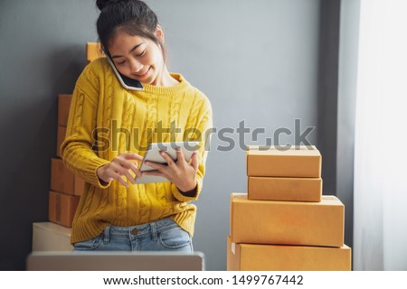 Startup small business SME, Entrepreneur owner using smartphone or tablet taking receive and checking online purchase shopping order to preparing pack product box. Selling online ideas concept