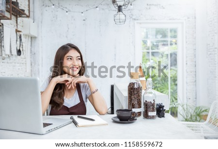 Startup successful entrepreneur small business owner SME asian woman sit look up in coffee shop restaurant. Portrait of young girl successful barista cafe local owner woman sme concept with copy space