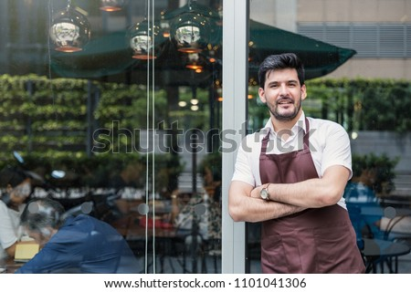 Startup successful small business owner man walking in his coffee shop or restaurant. Portrait of young caucasian man successful barista cafe local owner