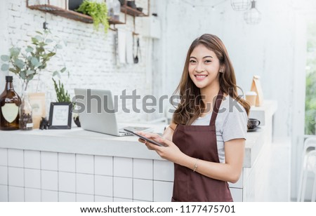 Startup successful small business owner sme beauty girl stand with tablet smartphone in coffee shop restaurant. Portrait of asian tan woman barista cafe owner. SME entrepreneur seller business concept