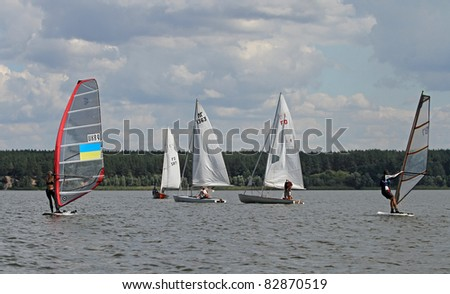 STARY SALTOV,UA - AUGUST 6: Class RS:X wind surfs unidentified participants compete during Slobozhanshina Sailing Cup. August 6, 2011 in Stary Saltov, Ukraine - stock photo