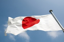 state Japanese flag on the strong wind over blue sky background