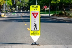 State Law Yield for Pedestrians Within Crosswalk reboundable road sign installed in the middle of the street