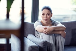 State of depression. Forlorn despaired woman sitting on sofa and hugging knees
