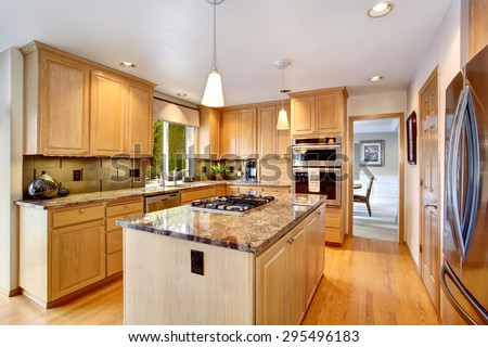 State Of The Art Kitchen With Hardwood Floor, Glossy Counters, And  Stainless Steel Fridge