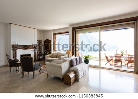 Stately living room with large windows overlooking the lake. Nobody inside