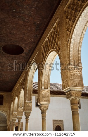 Stately, white, intricately carved, moorish arches of covered walkway in courtyard