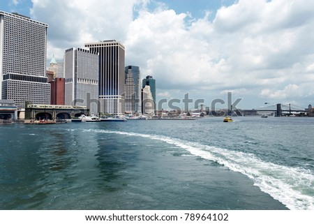 Staten Island Ferry's wake pulling away from the Governor's Island Ferry terminal with the Brooklyn Bridge and Lower Manhattan skyline