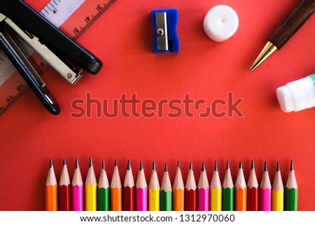 Stationaries such as colorful pensil, ruler, stapler, sharpener, pen amd glue shot on a plain isolated red background as wallpaper.
