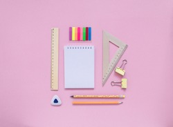 Stationary, back to school,creativity and education concept. Notebook, pen, pencil, eraser, ruler, paper clips, stapler, brush on pink background, flat lay.