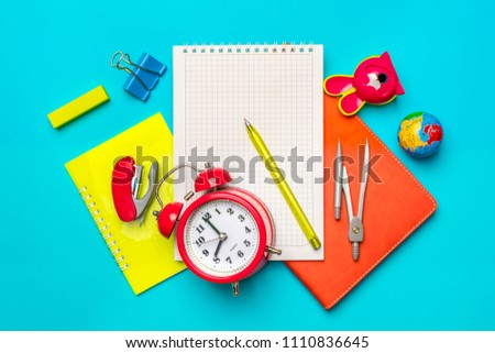 Stationary, back to school,summer time, creativity and education concept.School supplies-dividers, pencils, paper clips,note,stapler and notepad, globe on blue background,flatlay.Mock up.Top view