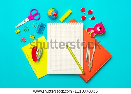 Stationary, back to school,summer time, creativity and education concept.School supplies -dividers, pencils, paper clips,note,stapler and notepad, globe on blue background,flatlay.Mock up.Top view