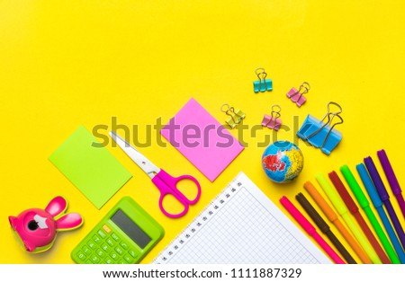 Stationary, back to school,summer time, creativity and education concept.School supplies scissors, pencils, paper clips,note,stapler and notepad, globe on yellow background,flatlay.Mock up.Top view