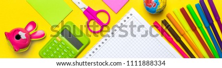 Stationary, back to school,summer time, creativity and education concept.School supplies scissors, pencils, paper clips,note,stapler and notepad, globe on yellow background.Mock up.Top view.Banner