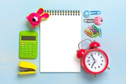 Stationary, back to school, summer time, creativity education concept School supplies, divider, calculator, paper clips, note, stapler, alarm clock, notepad on blue background, flat lay Mock up Top