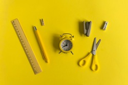 Stationary, business, back to school,creative and educational concept. Clean Notepad, pen, pencil, eraser, ruler, clothespin, clock, stapler, scissors on a yellow background, flat lay.