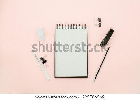 Stationary concept, Flat Lay top view Photo of pencils, paper clips, stapler and notepad  on pink background with copy space.Creative flat lay photo of workspace desk with  eyeglasses and notebook min