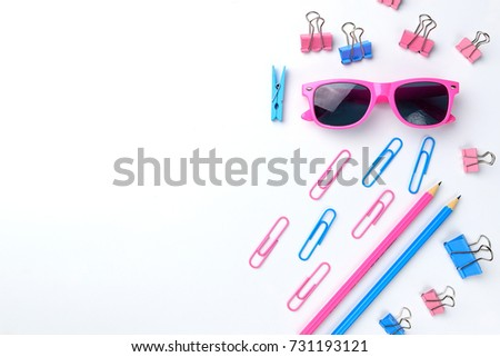 Stationary concept, Flat Lay top view Photo of Scissors, pencils, paper clips, sunglasses, sticky note paper,stapler in pink and blue tone on white background with copy space.