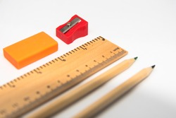 Stationeries Pencil, ruler, eraser and sharpner isolated on white background. Use of selective focus on a particular point on the ruler, with rest of the other items blurred.