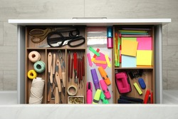 Stationery and sewing accessories in open desk drawer, top view
