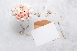 Stationery business flatlay creative composition. Top horizontal view of envelope, spiral blocj paper clips and a pen on abstract pink background