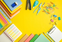 Stationery concept. Fat lay top view of notebook, clip board, colorful notepad, dividers, colorful pencils, paper clips, clip board with memo, dairy and stapler on yellow  background with copy space.