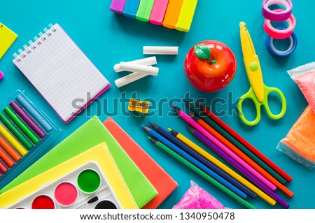 Stationery for study at school lies on blue. Back to school. Books and textbook, apple material for creativity. View from above.Rainbow color