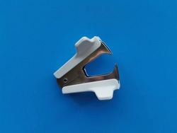 Stationery material.  Staple opener. Staple remover. Blue background.
