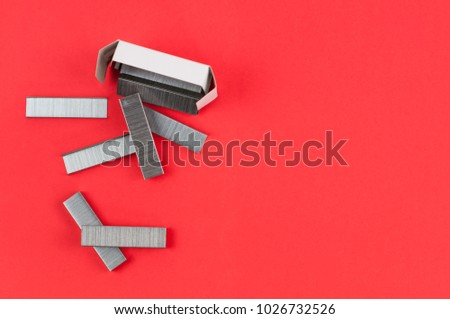 Stationery new metal clips for stapler poured out of cardboard box on red background
