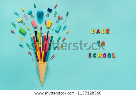 Stationery Pencils paintbrush paperclip in waffle ice cream cone. Text back to school Still life on blue background. Copy space Flat lay Top view Concept Education