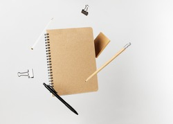 Stationery set. Levitation of notepad, pencils, pen, sticker and binder clips. Copy space on notebook and notes. Writing tools. Office supplies. Isolated on gray backdrop