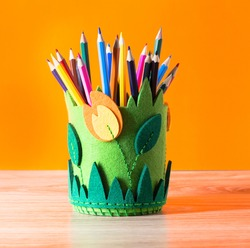 Stationery stand made of felt. Pencils on a wooden table.