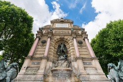 Statue and fountain at Place Saint-Michel with blue sky, Paris, France