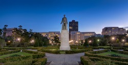 Statue and grave site of Huey Long on the grounds of the Louisiana State Capitol building at night in Baton Rouge, Louisiana