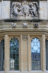 statue and stonework outside St John's college Oxford part of the university with the college coat of arms held by two angels or cherubs and Sir Thomas White's crest made in 1900