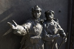 Statue as Communist propaganda - soviet soldier and civilian worker / laborer as builders of communism. Positive, heroic and visionary gesture (dramatic light, very low depth of field)