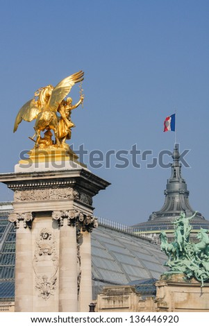 Statue at the Alexandre III bridge over the Seine in Paris, with the Grand Palais in the rear.