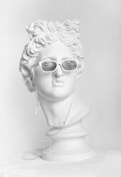 Statue. Earphone. Isolated. Gypsum statue of Apollo's head.Apollo Belvedere. Plaster statue of Apollo's head in earphones and white sunglasses. Head. Голова Аполлона Бельведерского из гипса. Clever.