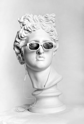 Statue. Earphone. Isolated. Gypsum statue of Apollo's head. Man. Creative. Plaster statue of Apollo's head in earphones and white sunglasses. Head. Black Lives Matter