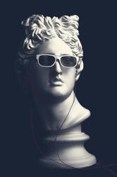 Statue. Earphone. Isolated. Gypsum statue of Apollo's head. Man. Creative. Plaster statue of Apollo's head in earphones and white sunglasses. Apollo Belvedere. Artwork