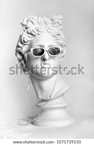 Statue. Earphone. Isolated. Gypsum statue of Apollo's head. Man. Creative. Plaster statue of Apollo's head in earphones and white sunglasses. Head.