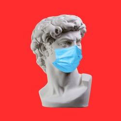 Statue. Earphone. Isolated. Gypsum statue of David's head. Man. Creative. Plaster statue of David's head in medical mask. Minimal concept art.